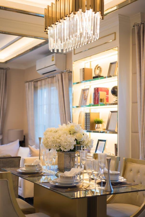 Ställ in av den eleganta tabellen i modern matsal med den lyxiga tabelluppsättningen arkivfoto