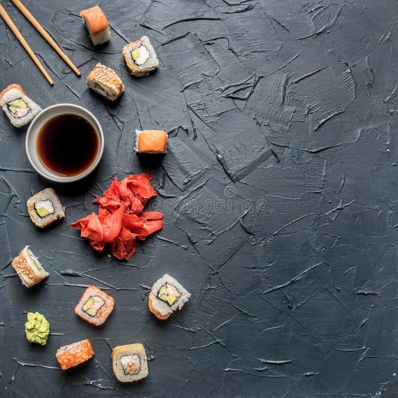 Ställ in av den läckra sushi med ingefäran och wasabi på en grå bakgrund, utrymme för text royaltyfria bilder