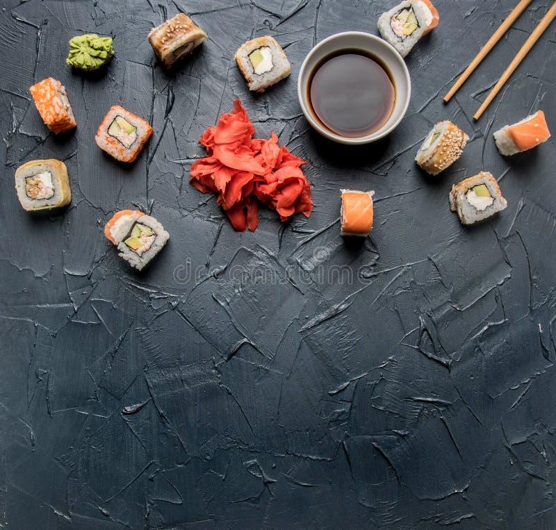 Ställ in av den läckra sushi med ingefäran och wasabi på en grå bakgrund, utrymme för text royaltyfri foto