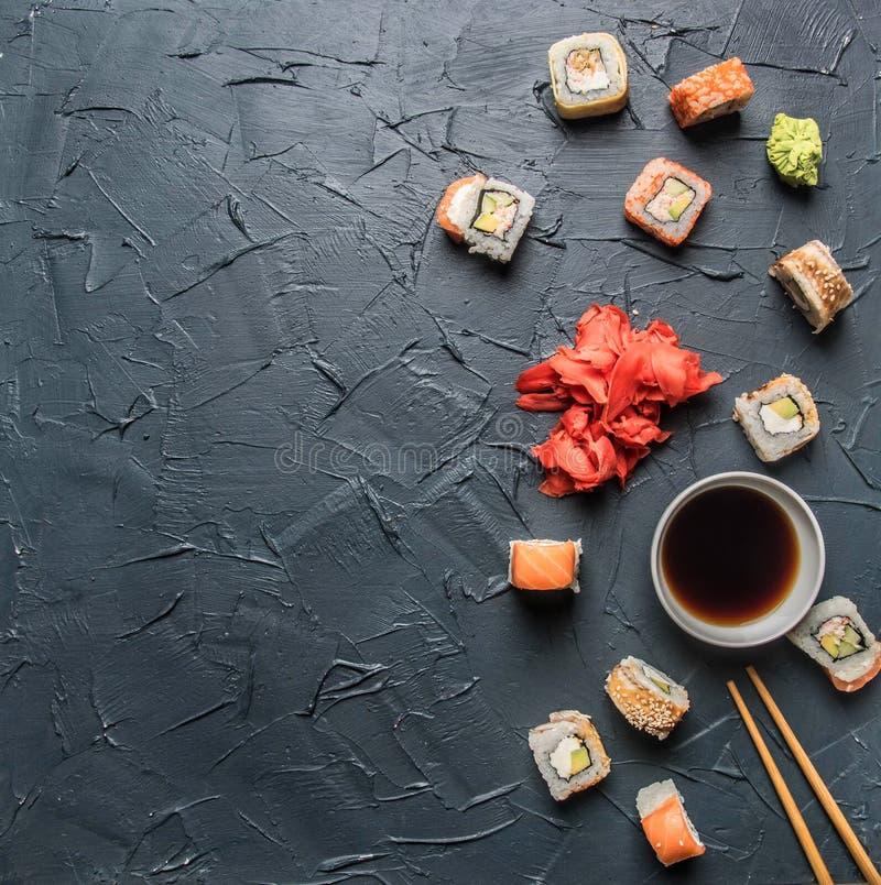 Ställ in av den läckra sushi med ingefäran och wasabi på en grå bakgrund, utrymme för text royaltyfria foton