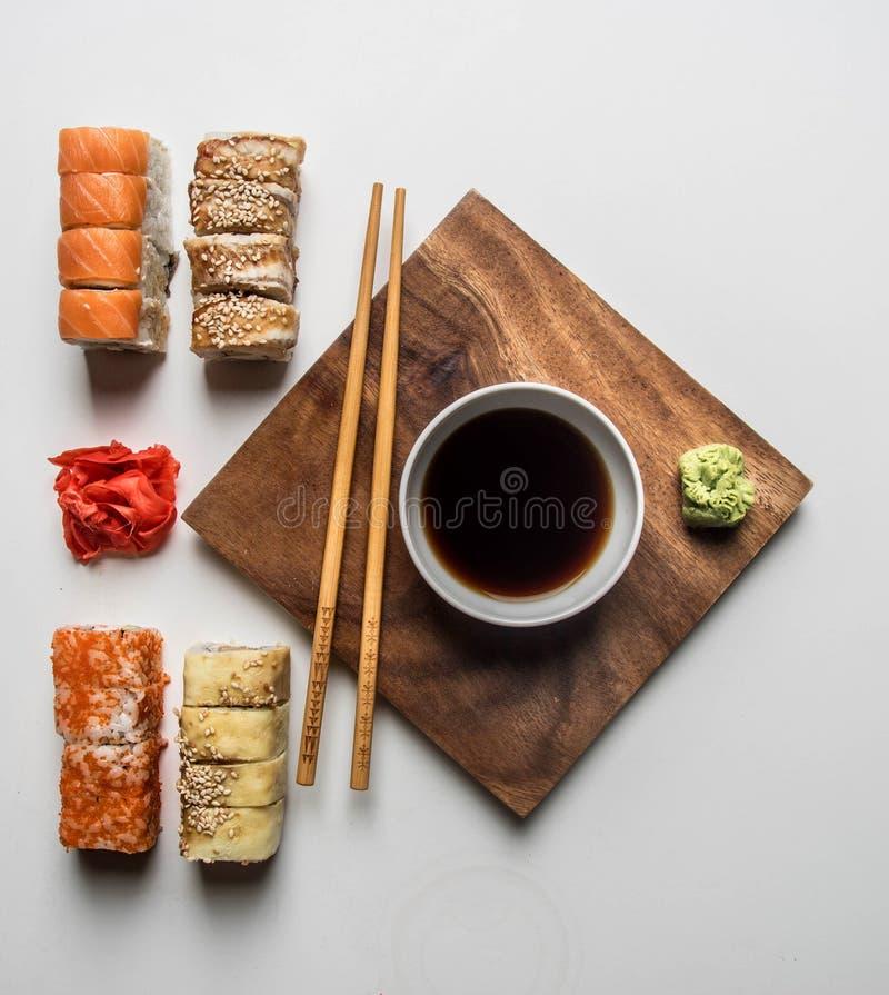 Ställ in av den läckra sushi med ingefäran, soya och wasabi på en vit bakgrund royaltyfri bild