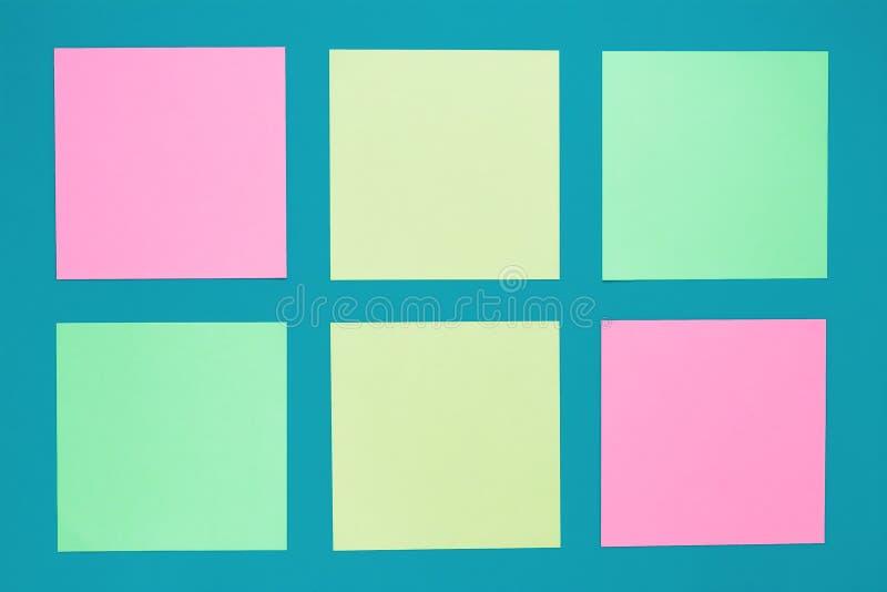 Ställ in av färgrika klibbiga anmärkningar på turkosbakgrund Mångfärgade klistermärkear med kopieringsutrymmen på blått bräde Tom royaltyfri foto