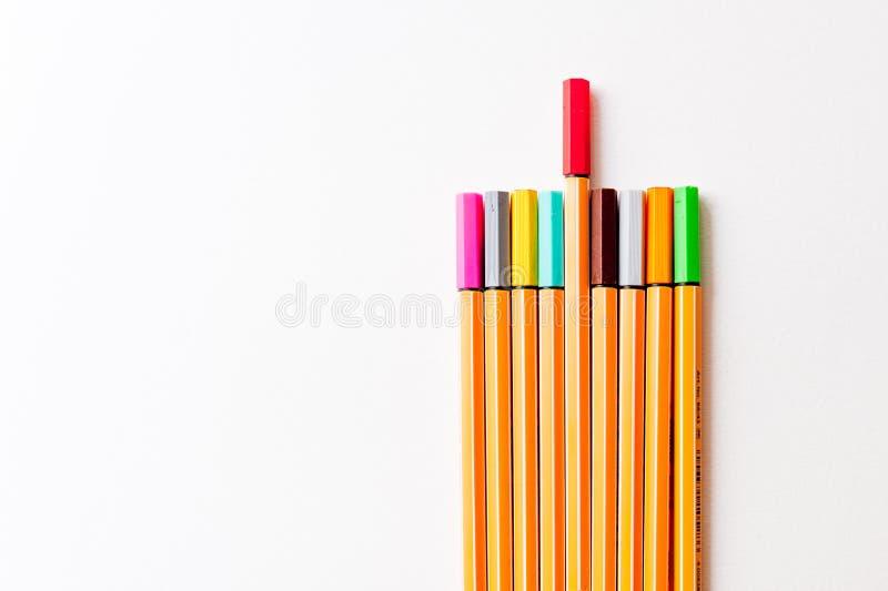 Ställ in av färgrika markörer som ett symbol av unikhet och egenart på vit bakgrund med en som är högre än andra royaltyfria bilder