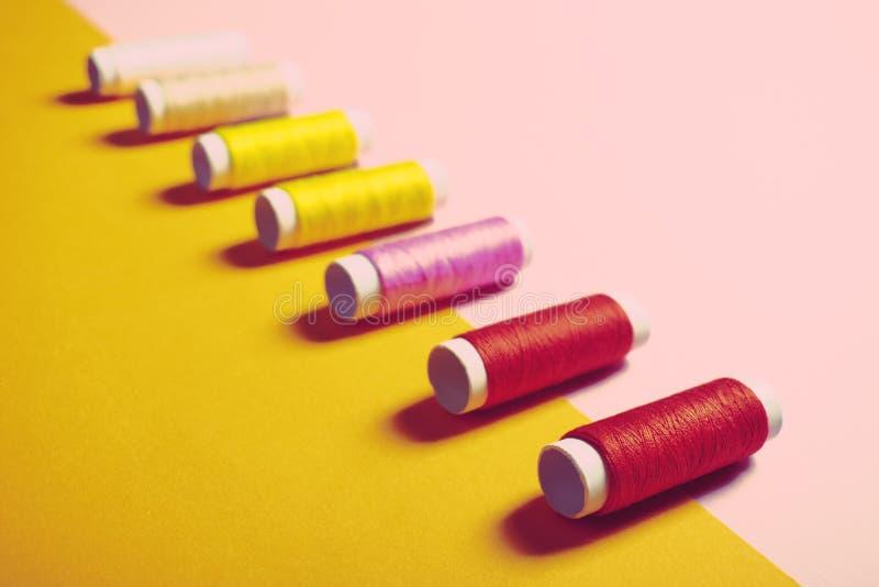 Ställ in av färgrika sy trådar på ljus bakgrund royaltyfri foto