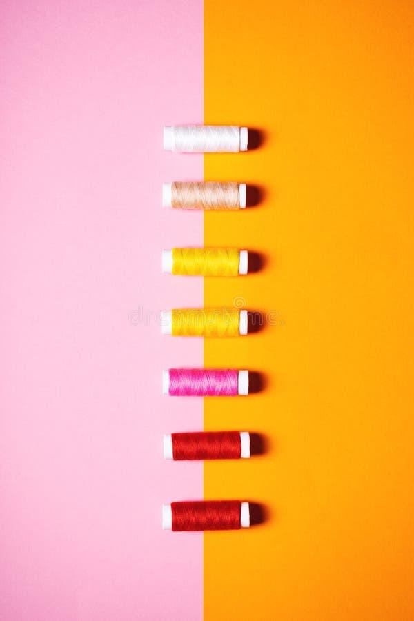 Ställ in av färgrika sy trådar på ljus bakgrund fotografering för bildbyråer