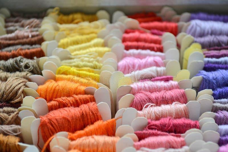 Ställ in av färgrika trådar i varma färger för broderi och sycloseupen royaltyfri bild