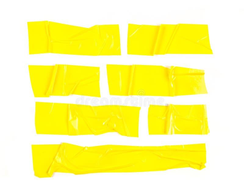 Ställ in av gula band på vit bakgrund Sönderrivet gult klibbigt band för horisontal- och olikt format, självhäftande stycken fotografering för bildbyråer
