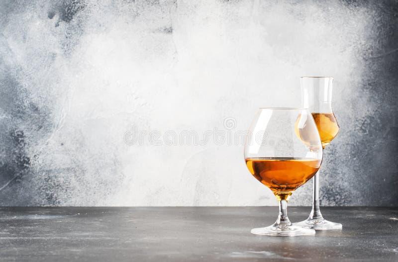 Ställ in av hårda starka alkoholdrycker och andar i exponeringsglas i sortiment: vodka, konjak, konjak och whisky, grappa Grå fär royaltyfria foton
