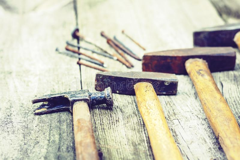 Ställ in av hjälpmedel för tappninghandkonstruktion som hammare med spikar på en träbakgrund, retro begrepp arkivfoton