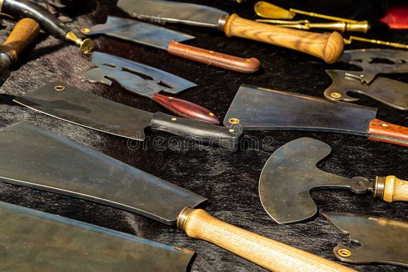 Ställ in av köttknivar som den kulinariska yxan vässade det breda bladvalet för varje smak på en svart bakgrundsmagasingevärssmed royaltyfri bild