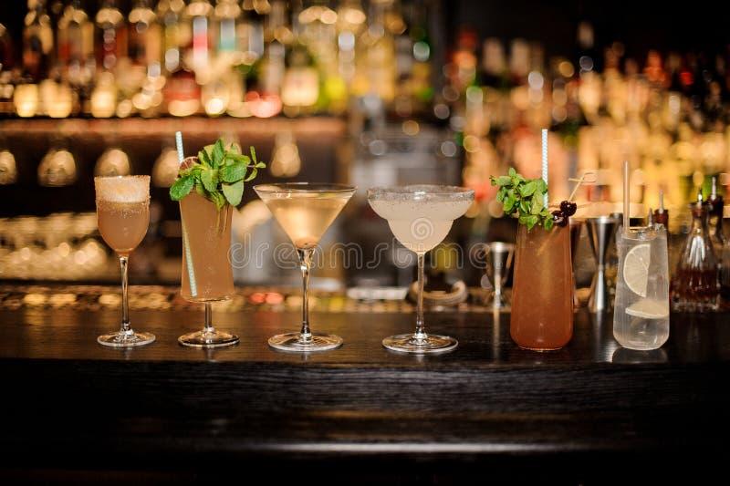 Ställ in av klassiska coctailar: Smutsiga Martini, Sherry Cobbler, Brandy Crusta, margarita, kobrahuggtand och Tom Collins arkivbilder