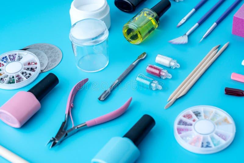 Ställ in av kosmetiska hjälpmedel för yrkesmässig manikyr och att spika omsorg på blå bakgrund Top beskådar royaltyfri fotografi
