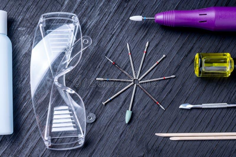 Ställ in av kosmetiska hjälpmedel för yrkesmässig maskinvarumanikyr på en mörk bakgrund Malningskärare, exponeringsglas, bästa si arkivbild