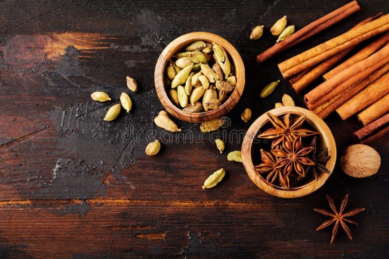 Ställ in av kryddor av stjärnaanis, kardemumman, kanel och farin på gammal träbakgrund royaltyfri fotografi