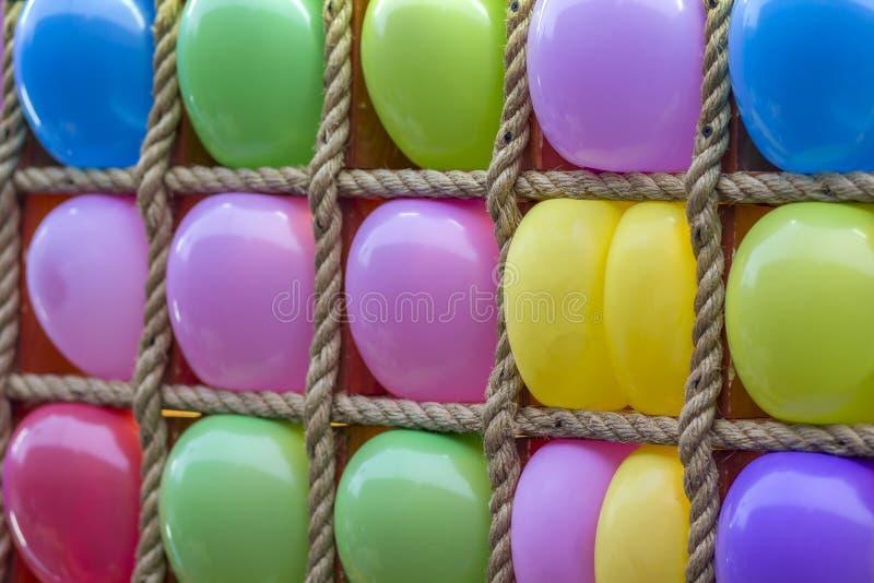 Ställ in av ljusa färgrika ballonger som ordnas i repram till salu Dekorativ mångfärgad kopieringsspaceibakgrund, födelsedagparti arkivbild