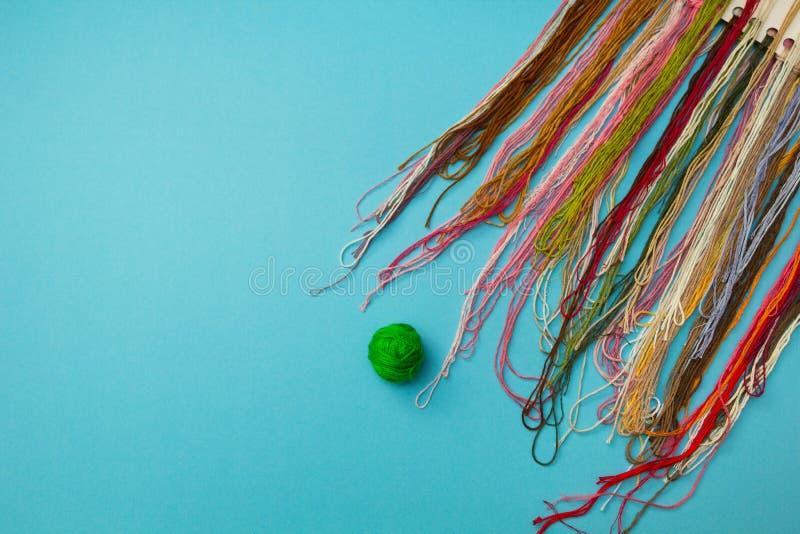 Ställ in av mång--färgade trådar på ett mörkt - blå randig bakgrund royaltyfri fotografi