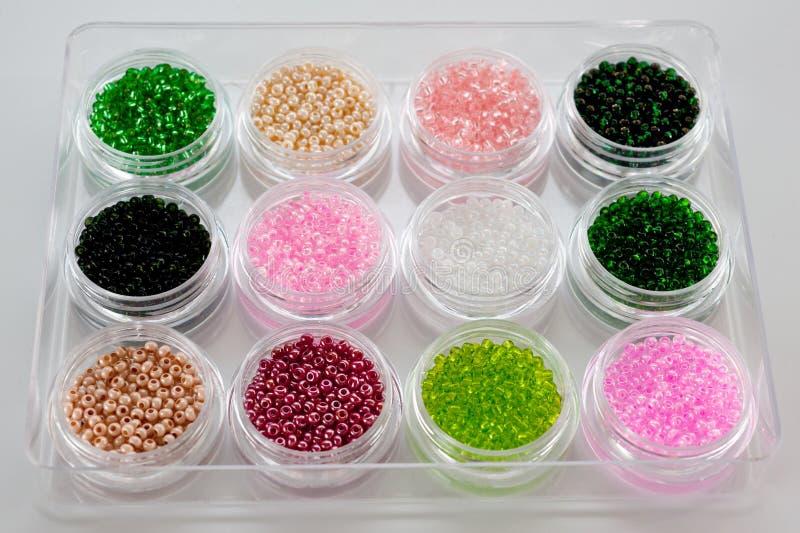 Ställ in av mångfärgade pärlor för broderi och handarbete i plast- krus arkivfoton