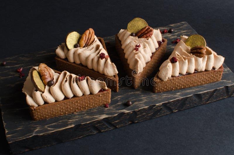 Ställ in av mini- tarts för choklad som dekoreras med pecannötmuttrar royaltyfri bild