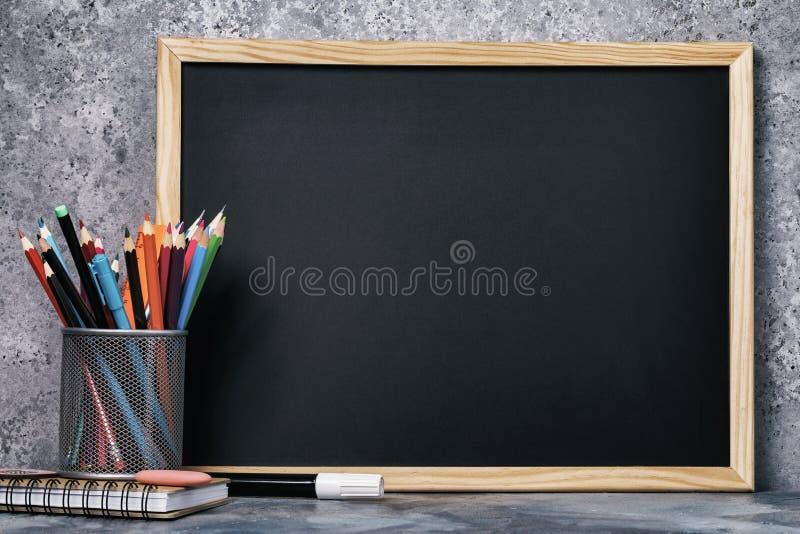 Ställ in av olika blyertspennor, pennor och ett kritabräde med kopieringsutrymme royaltyfri bild