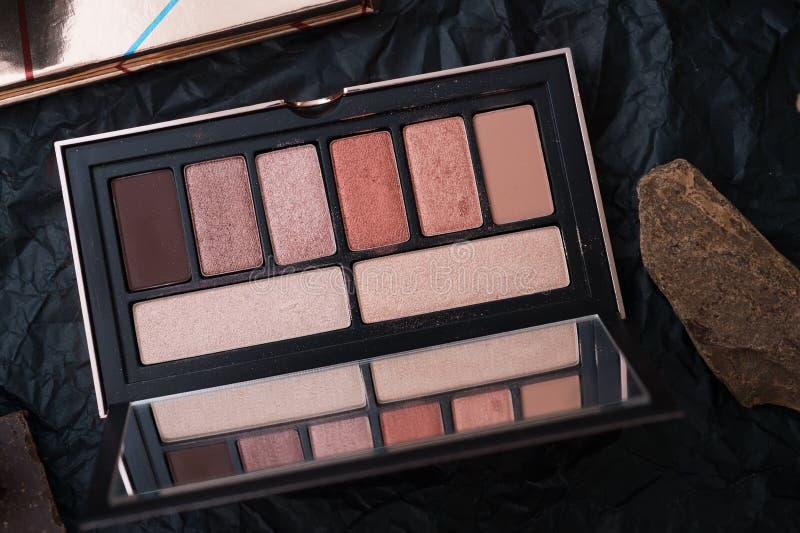 Ställ in av paletten för ögonskugga och naturchoklad på svart bakgrund i ram arkivbild
