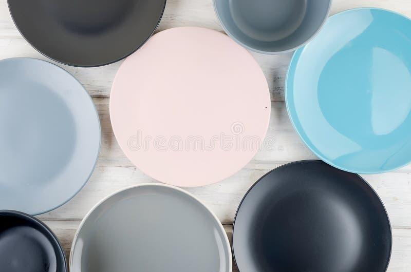 Ställ in av pastellfärgad färg för ren bordsservis på träbakgrund royaltyfri bild