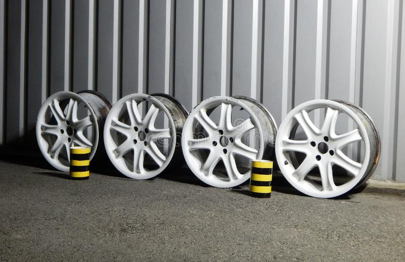 Ställ in av Rusty Damaged Alloy Wheel Rims i garage royaltyfria foton