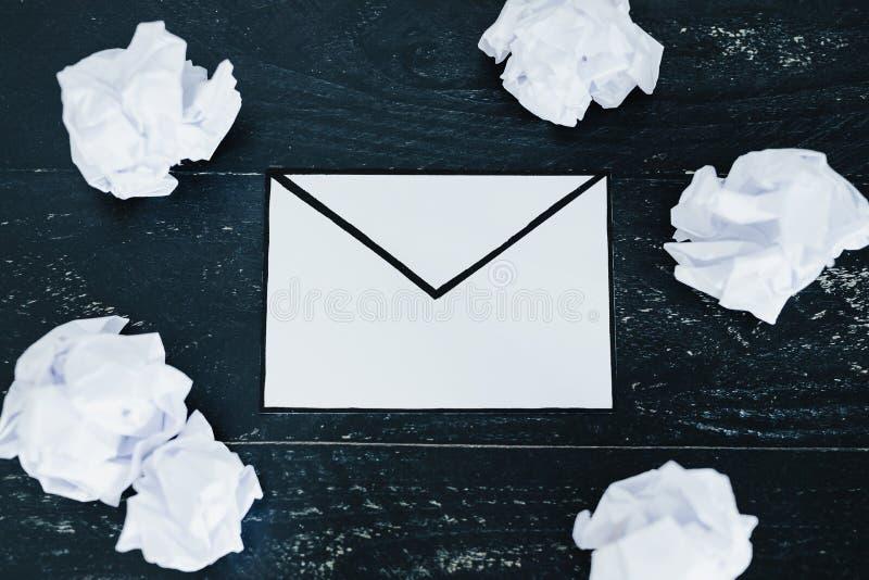 Ställ in av scrunched pappers- bollar och email- eller bokstavskuvert på mörk lynnig bakgrund royaltyfria foton
