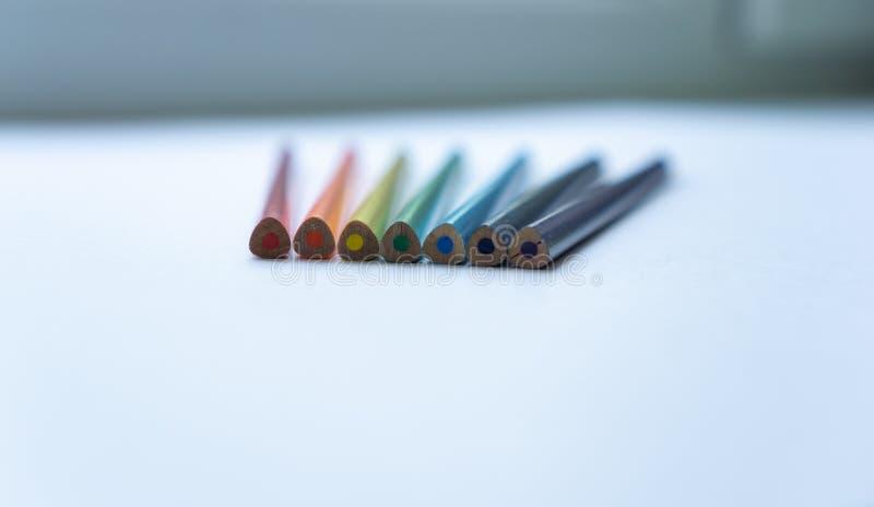 Ställ in av sju inte vässade regnbåge-färgade blyertspennor på en vit bakgrund Selektivt fokusera arkivbild