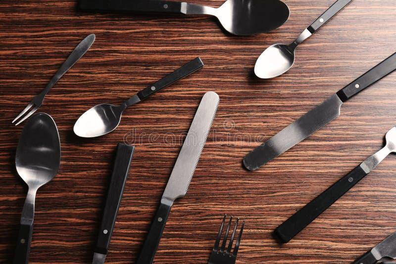 Ställ in av skedar, gafflar och knivar på träbakgrund royaltyfri fotografi