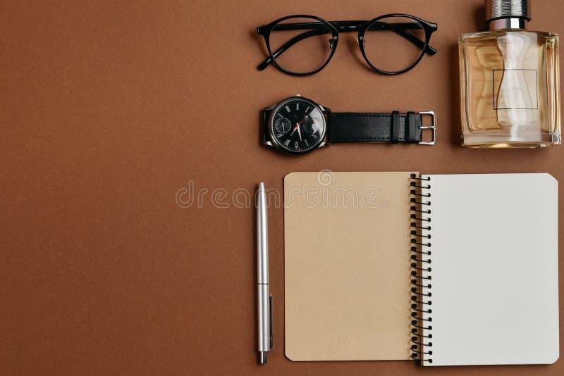 Ställ in av stilfull manlig tillbehör med en penna, en doft, en klocka, en notepad och exponeringsglas på brun bakgrund Minsta be arkivfoto