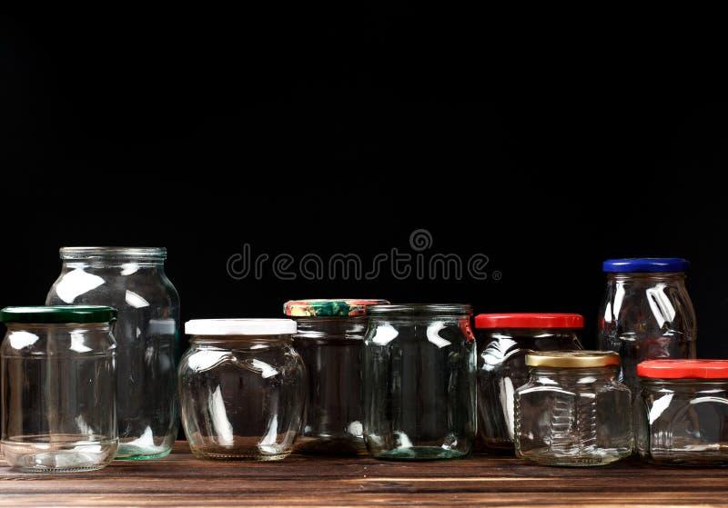 Ställ in av tomma exponeringsglaskrus för beskydd, på svart bakgrund - bild royaltyfri fotografi