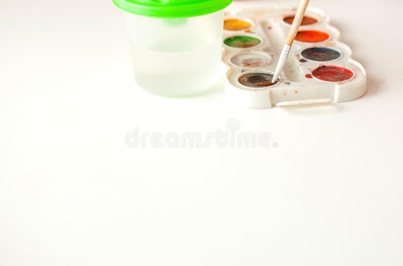 Ställ in av vattenfärgmålarfärger och målarpenslar för att måla på den vita bakgrundscloseupen, kopieringsutrymme Selektivt fokus arkivfoto