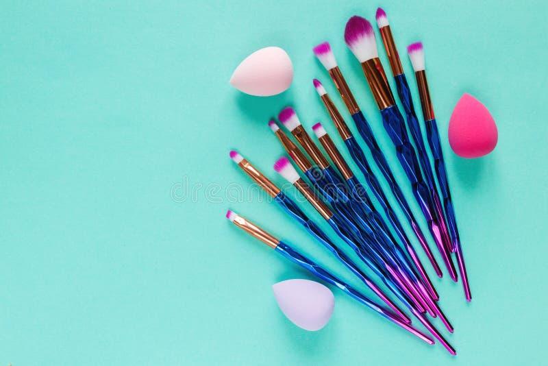 Ställ in av violetta purpurfärgade metalliska makeupborstar för olikt yrkesmässigt moderiktigt mode på pastellfärgad grön bakgrun royaltyfria foton