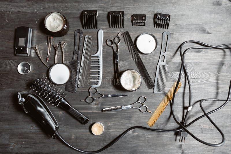 Ställ in av yrkesmässiga frisörhjälpmedel på grå bakgrund Trätabell i frisersalong Arbetehjälpmedel av barberareförlagen royaltyfri foto