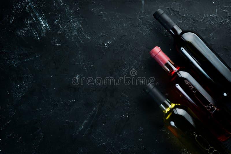 Ställ in en flaska av vitt vin som är röd och, steg vin på en svart stenbakgrund royaltyfri bild