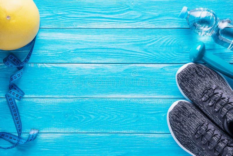 Ställ in för sportaktiviteter på blå träbakgrund sund livsstil för begrepp Sportutrustning, matt yoga, sportskor som mäter royaltyfria bilder
