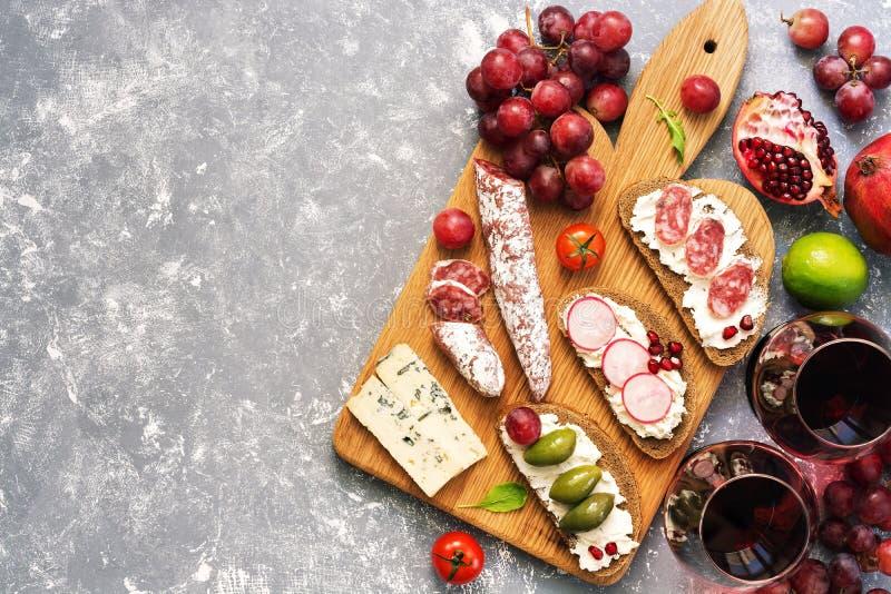 Ställ in från en variation av mellanmål, Bruschetta eller autentiska traditionella spanska tapas, rött vin och druvor på en grå b royaltyfria foton