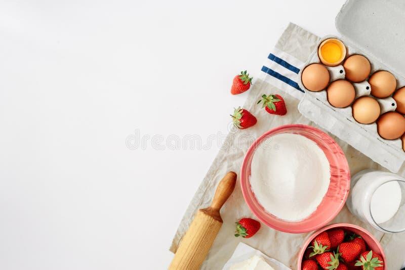 Ställ in ingredienser som lagar mat boren för bakgrund för jordgubbepajkakan den vita arkivfoton
