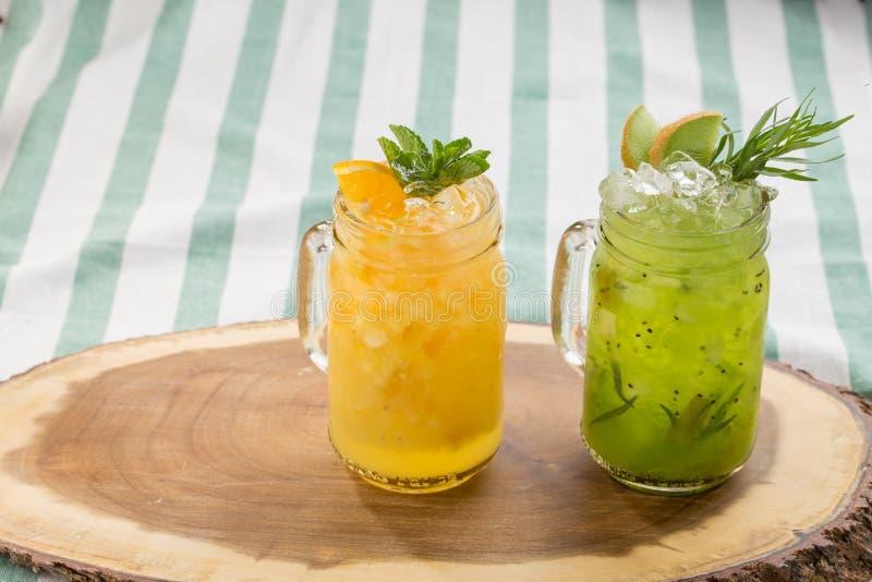Ställ in kall lemonad med citronen, apelsinen och kiwin på träbräde på randig textilbakgrund royaltyfri fotografi