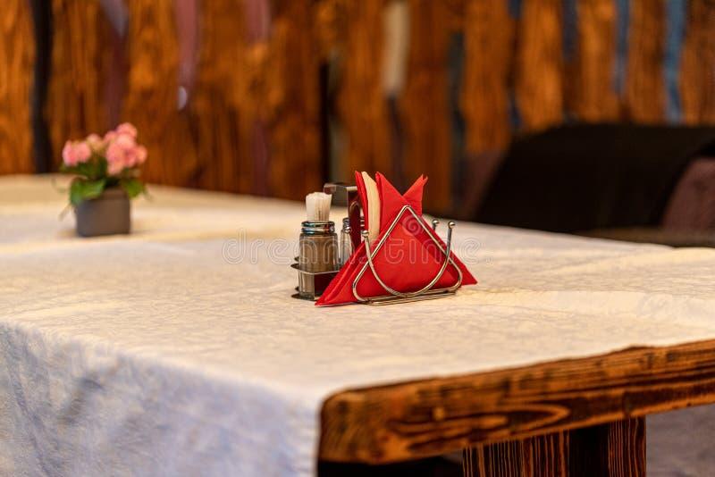Ställ in med servetter, kryddor och tandpetare i en metallställning på en vit bordduk Selektivt fokusera 3d mot v?ggen f?r visual royaltyfri foto