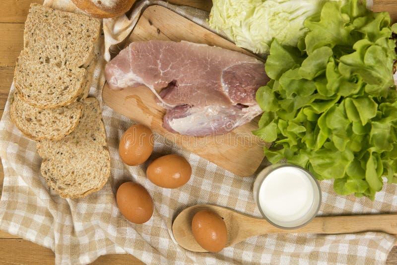 Ställ in produkter som består av bröd, mjölka, griskött, ägg och grönsaken på trätabellen arkivfoto