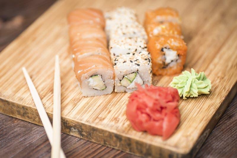 Ställ in sushirullar med laxen, sesam, den röda kaviaren, avokadot, ingefäran, wasabi och pinnar för sushi arkivfoto