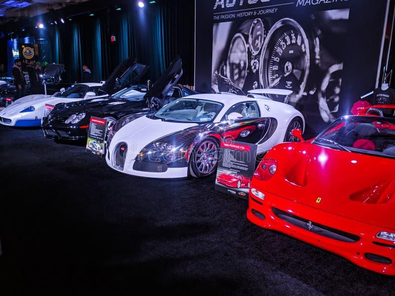 Ställ upp av mycket snabba toppna bilar på skärm såväl som en svart bentley arkivfoton