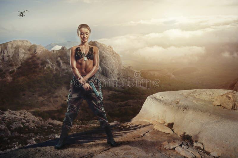 Ställa till upplopp flickan på en stenig avsats med ett vapen arkivfoton