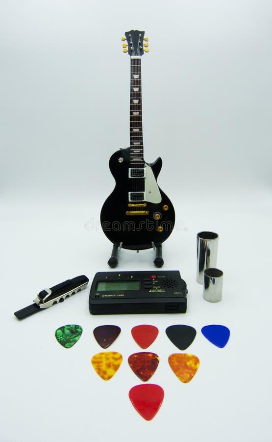 Ställa in - upp gitarren, gitarrstämmaren, plektra, flaskhalsar och metallgitarrcapoen royaltyfria bilder