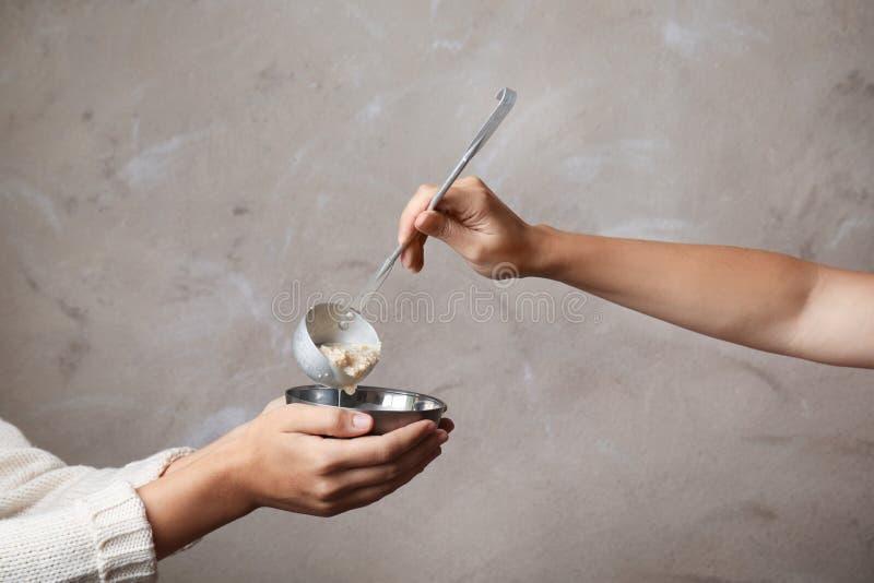 Ställa upp som frivillig sätta mat in i bunken av den fattiga kvinnan på färgbakgrund, closeup arkivfoton