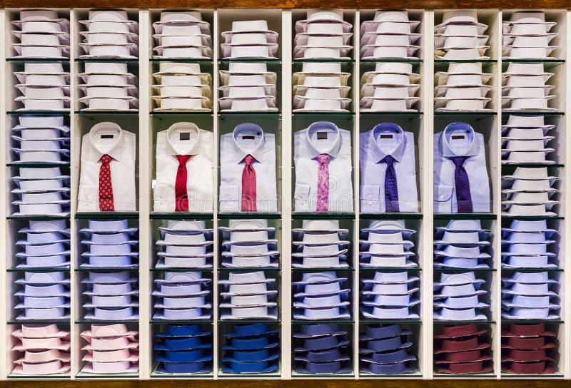 Ställa ut med många olika färgrika vikta manliga modeskjortor för vuxen samling i materiel på hyllor i menswear royaltyfri bild