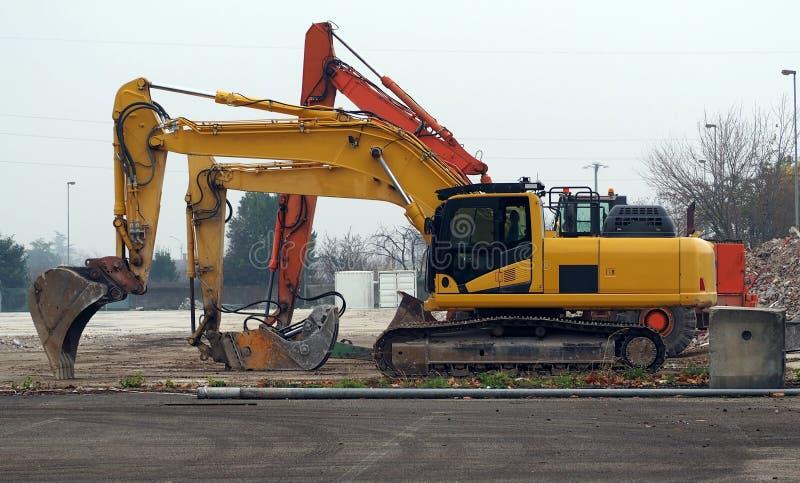 Ställde upp stor grävskopa tre i en dimmig dag på konstruktionsplatsen royaltyfri foto