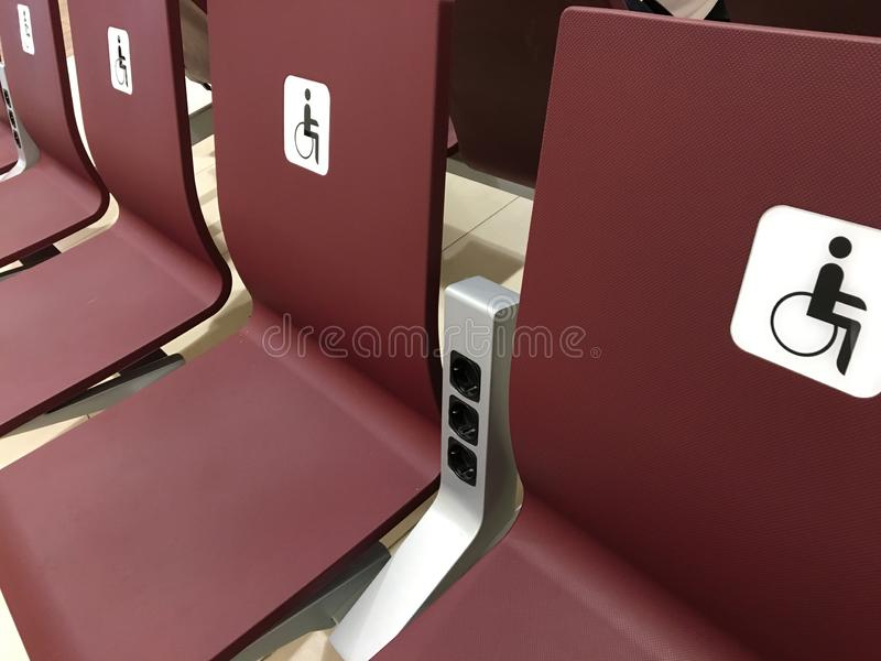 Ställe för ogiltigt platser för handikappade personer, stolar i korridoren för specialt folk arkivfoton