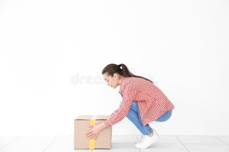 Ställingsbegrepp Ung kvinna som lyfter den tunga kartongen royaltyfri fotografi